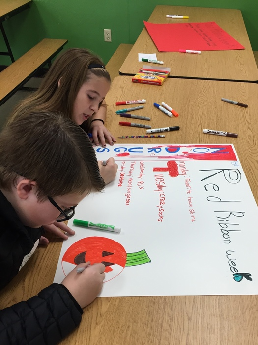 Sixth-grade ambassadors celebrated Red Ribbon Week by making posters and reading to kindergarten students.